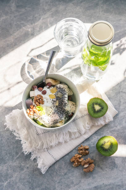 Fruit salad with yogurt in a bowl served for breakfast in sunlight stock photo