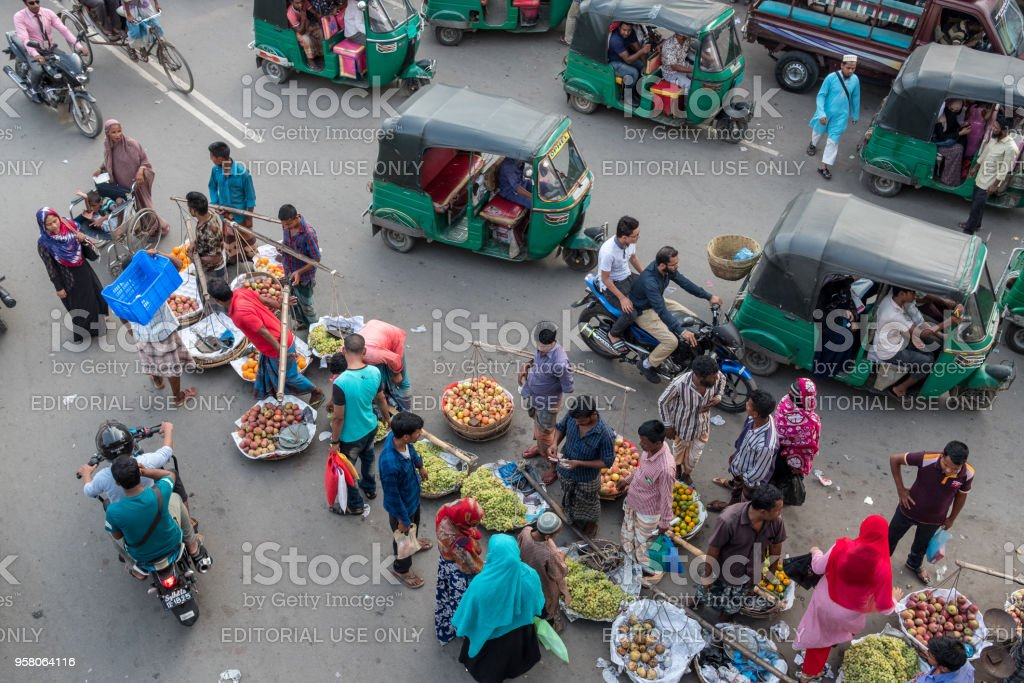 Fruit sellers and rickshaws on the streets of Sylhet. stock photo