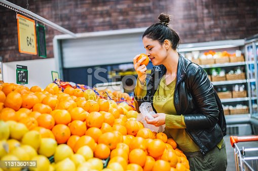 A young woman, housewife, decided to go to the supermarket and buy groceries for his family. the will to cook breakfast, lunch, dinner and everything she wrote on her shopping list. She chooses, fruits, vegetables, wine, cosmetics.
