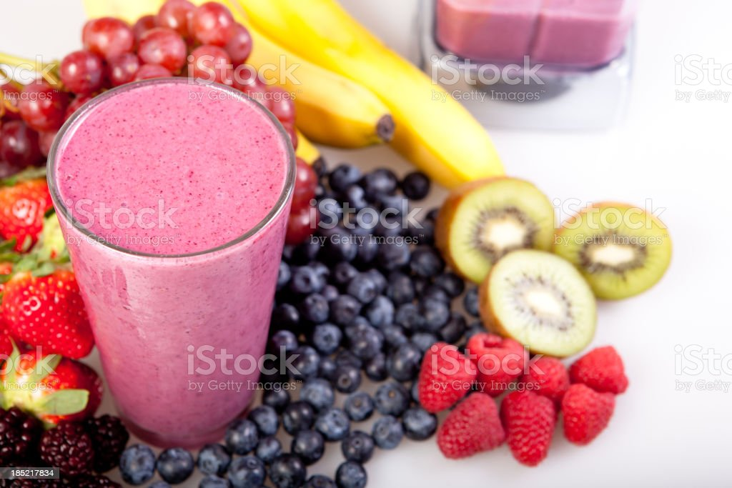 A fruit smoothie with fruit around it stock photo