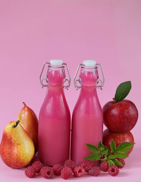 frucht-smoothies. gesunde smoothie. rosa smoothies aus äpfeln, birnen und beeren himbeeren auf einem hellen rosa hintergrund gemacht. - birnen rezepte stock-fotos und bilder
