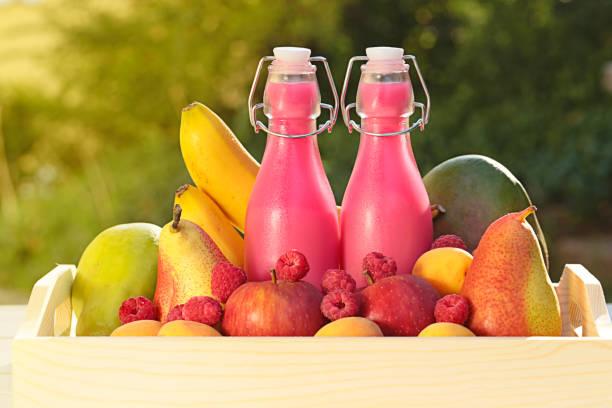 frucht-smoothies. gesunde smoothie. rosa smoothies aus frischen äpfeln, birnen und beeren himbeeren, banane und mango in ein holztablett auf einem hintergrund verschwommen pflanze hergestellt - birnen rezepte stock-fotos und bilder