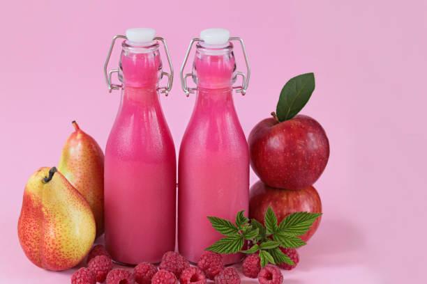 frucht-smoothies. gesunde smoothie. rosa smoothies aus frischen äpfeln, birnen und beeren himbeeren auf einem hellen rosa hintergrund gemacht. - birnen rezepte stock-fotos und bilder