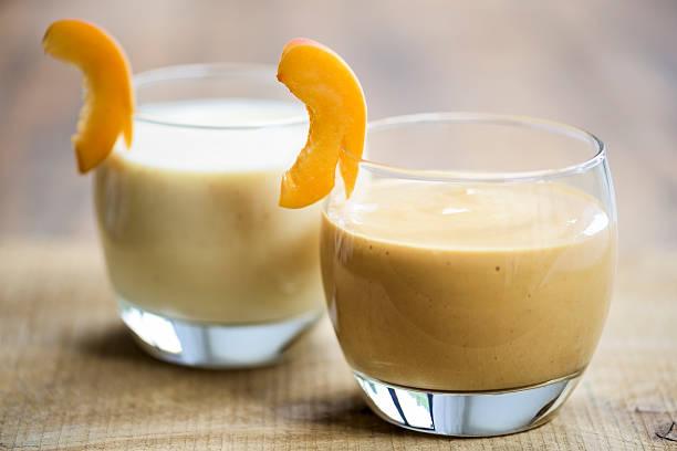 fruit smoothies in short round glasses on a wooden background - pfirsich milchshake stock-fotos und bilder