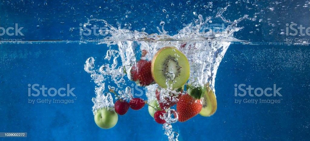 plum in water, strawberry, kiwi, cherry, blue background