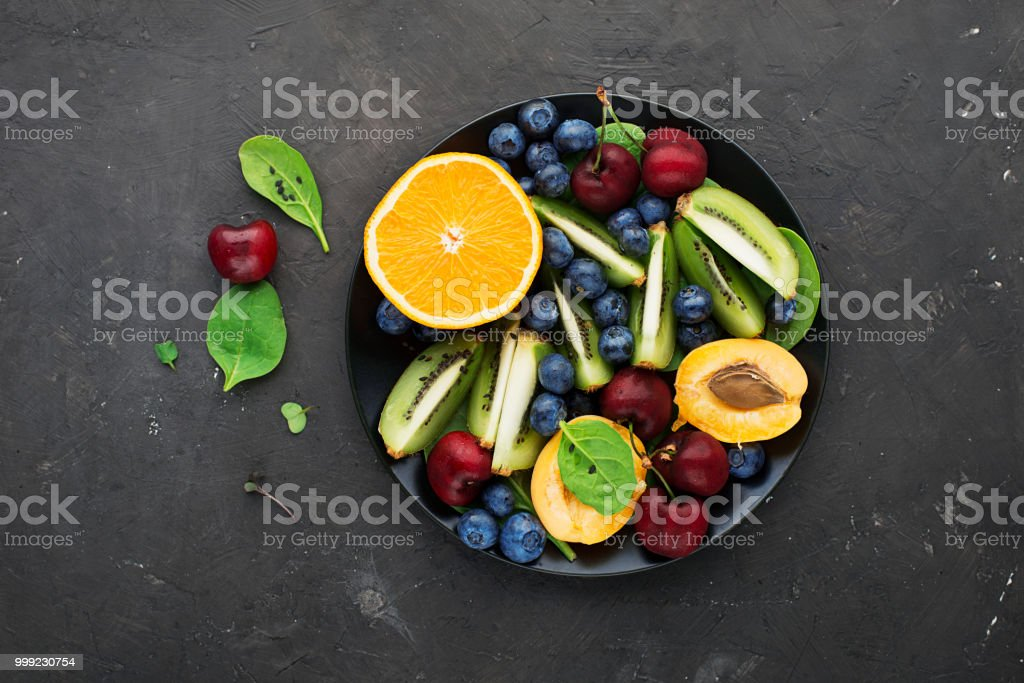 Fruit summer bowl. Orange, kiwi, cherry, spinach, blueberry, apricot plate. Top View stock photo