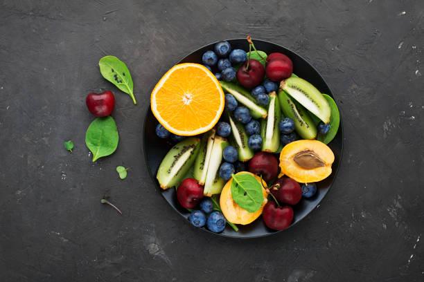 sommer obstschale. orange, kiwi, kirsche, spinat, heidelbeeren, aprikosen platte. ansicht von oben - obstkorb stock-fotos und bilder