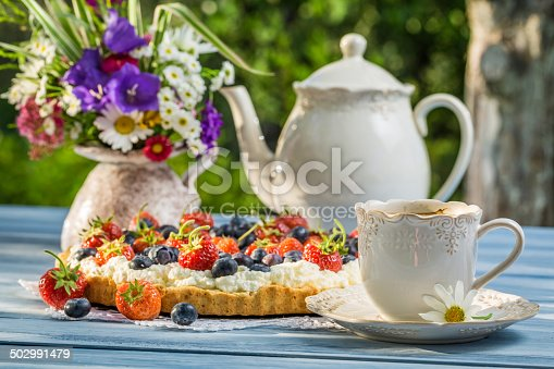 502634476 istock photo Fruit tart served with coffee in the summer garden 502991479