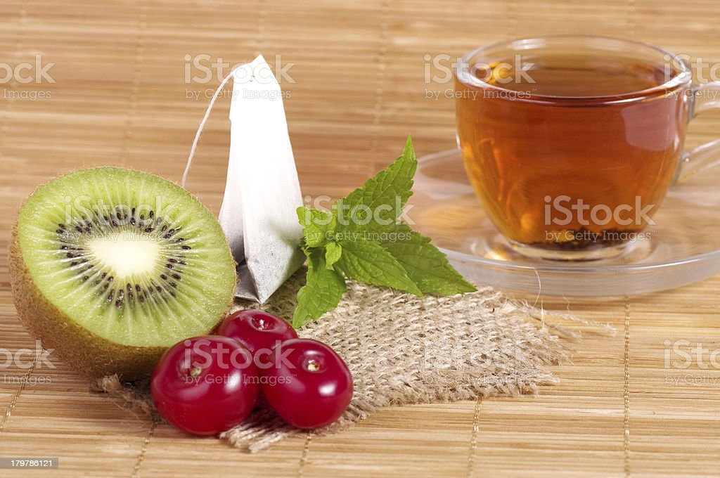 Fruit tea in cup with cherry and kiwi royalty-free stock photo