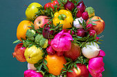 An amazing colorful composition of a variety fresh fruits and vegetables, pink peonies and green leaves on a green background. The concept of a healthy food and lifestyle. Top view, closeup
