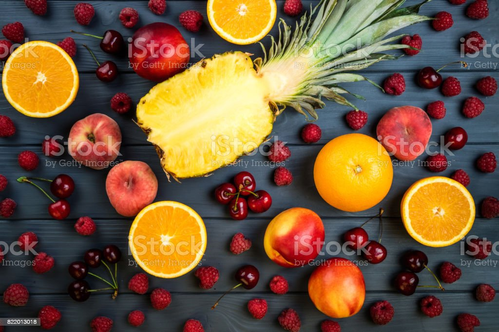 Fruits and berries. Assortment of exotic fruits. Pineapple, raspberries, peach, kiwi, citrus and cherry. Flat lay, top view stock photo