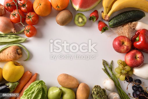 istock Fruits and vegetables around a white table top view 680283572