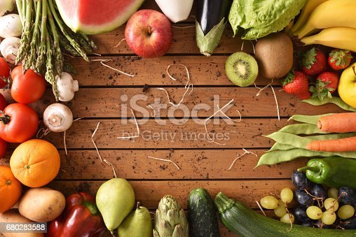 istock Fruits and vegetables around a wood table top view 680283588