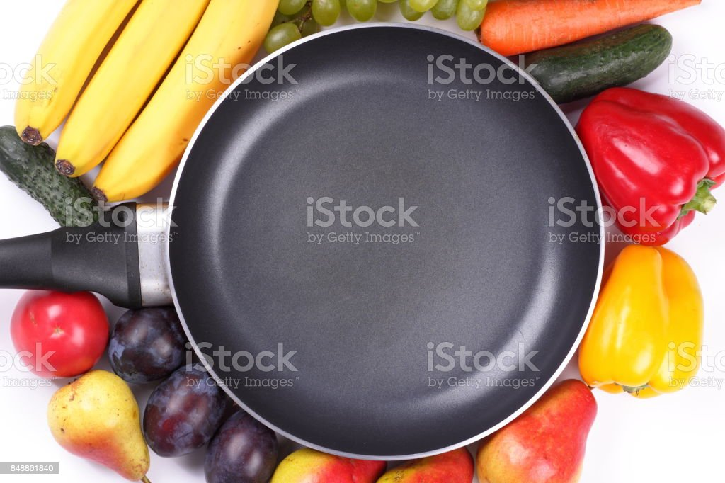 Fruits and vegetables around an empty frying pan with a place for an inscription for the designer stock photo