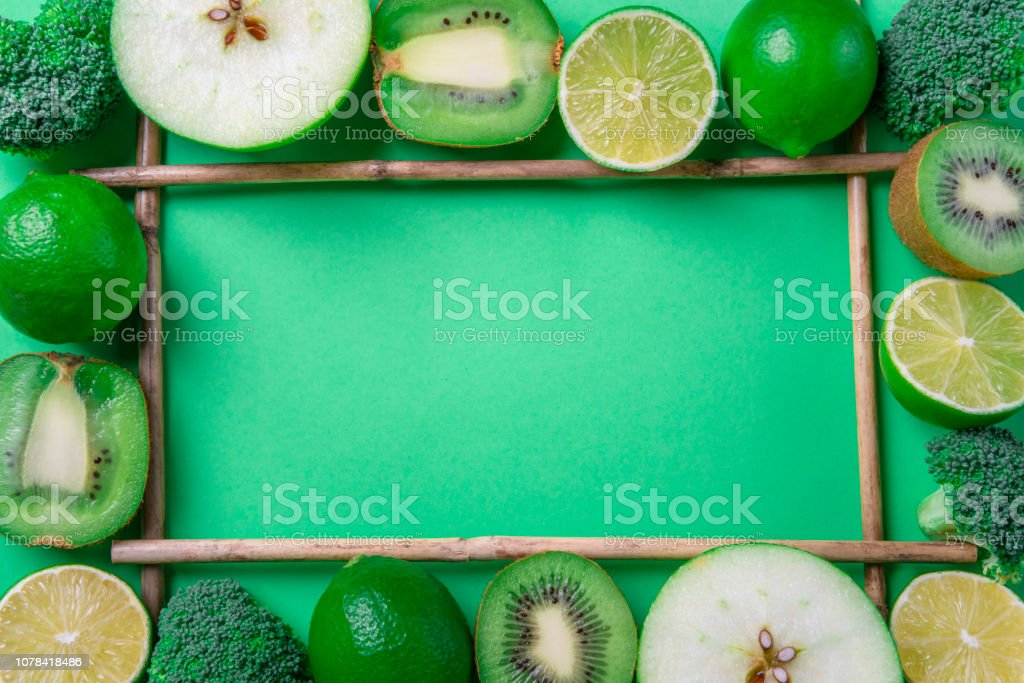 Fruits and vegetables frame on a green background. Above view with copy space in the center stock photo