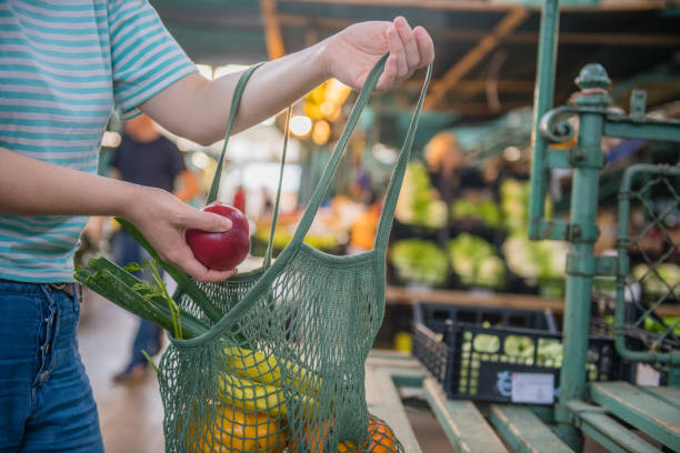 fruits and vegetables in a cotton mesh reusable bag, zero waste shopping on outdoors market - mercato frutta donna foto e immagini stock