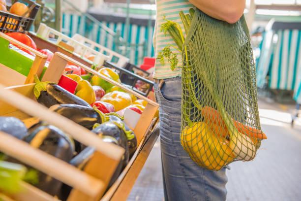 fruits and vegetables in a cotton mesh reusable bag, zero waste shopping concept - rifiuti zero foto e immagini stock