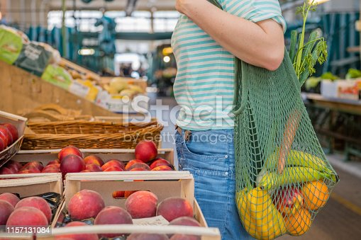 Fruits and Vegetables in a cotton mesh reusable bag, Zero Waste Shopping concept at public outdoors market.
