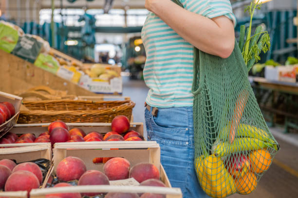 fruits and vegetables in a cotton mesh reusable bag, zero waste shopping concept - ambientalista foto e immagini stock