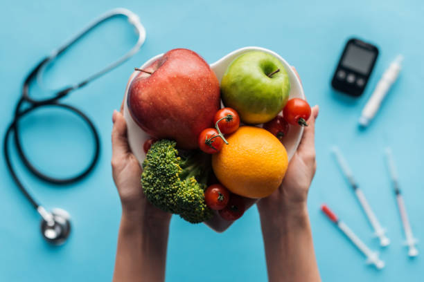 fruits and vegetables in female hands with medical equipment on blue background - diabetes стоковые фото и изображения