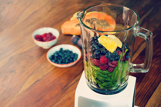 Fruits and vegetables in the blender Fruits and vegetables as ingredients for a healthy smoothie: papaya, figs, lemon, blueberries, pomegranate seeds, raspberries, pineapple and baby spinach blender stock pictures, royalty-free photos & images