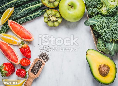 Fruits and vegetables ingredients frame for healthy diet top view on white marble table copy space.