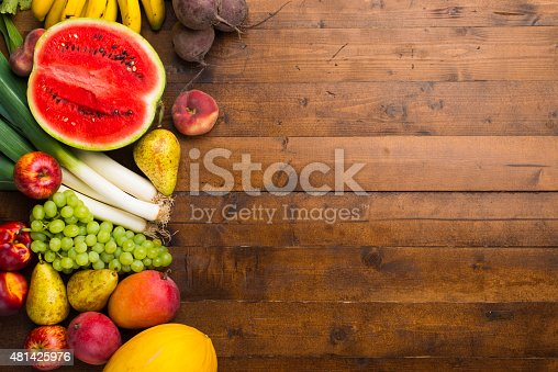 Various fruits and vegetables arranged on a wooden table.