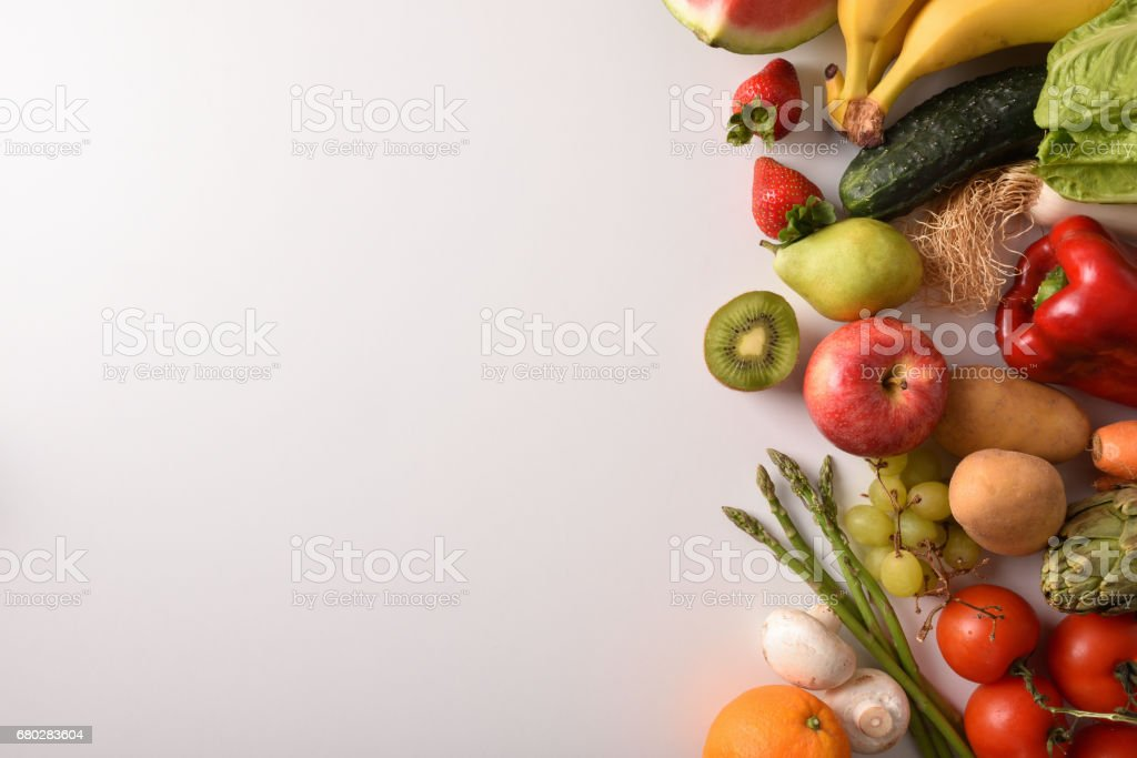 Fruits and vegetables on a white table top view stock photo