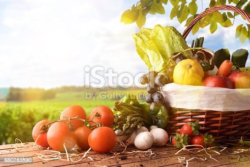 istock Fruits and vegetables on table and crop landscape background lateral 680283590