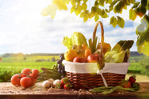 Assortment of fruits and vegetables in a wicker basket on a wooden table on crop landscape background. Horizontal composition. Front view