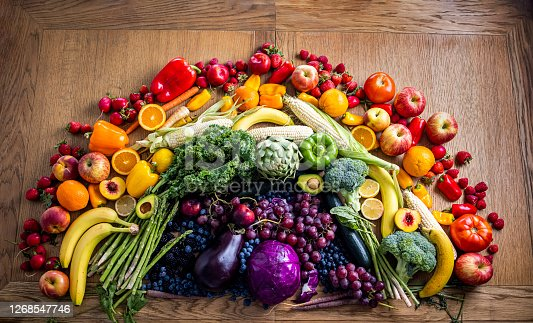 A rainbow of fruits and vegetables on a wooden table.