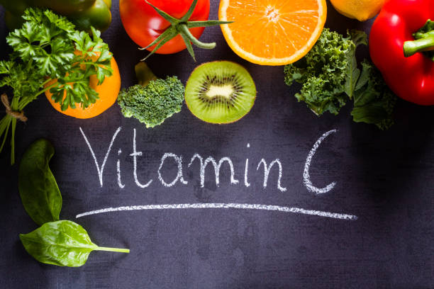 Fruits and vegetables rich in vitamin c with white word inscription by chalk. stock photo