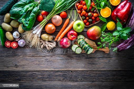 Fruits and vegetables vegetarian food on rustic wood board with copy space