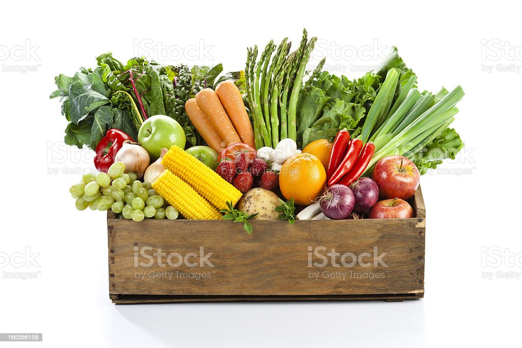 Fruits and veggies in wood box with white backdrop stock photo
