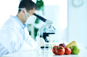Scientist examining genetically modified fruits and vegetables at laboratory