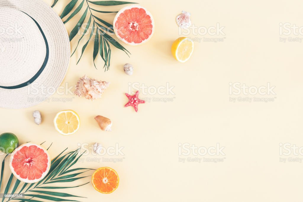 Fruits, hat, tropical palm leaves, seashells. Flat lay, top view stock photo