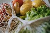 fruits lemon , carrot, apple, vegetables, banana, tomato inside of reusable bag on dining table with high angle view