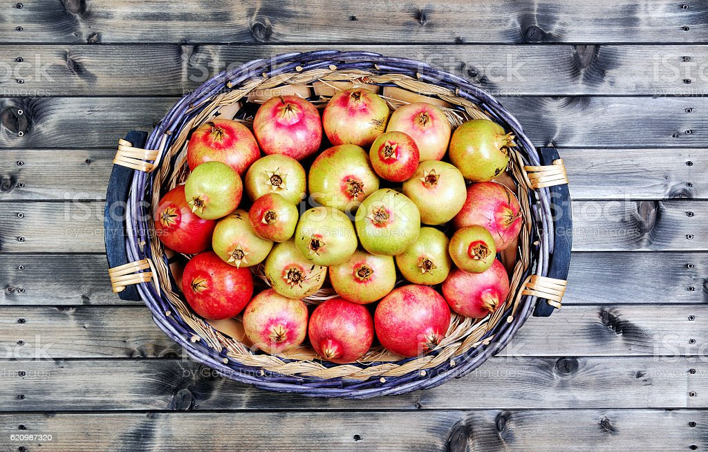 Fruits of ripe pomegranate in a wicker basket foto royalty-free