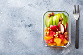 Fruits salad and nuts in a glass container. Healthy eating. Grey background. Copy space. Top view.