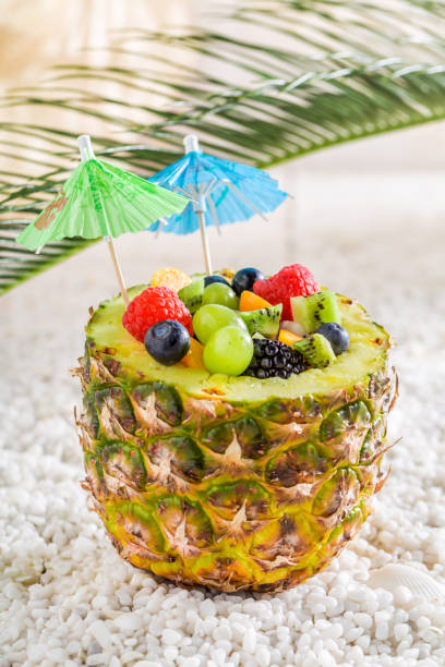obst salat in ananas mit cocktail sonnenschirme am weißen kieselsteinen - hawaiianischer salat stock-fotos und bilder