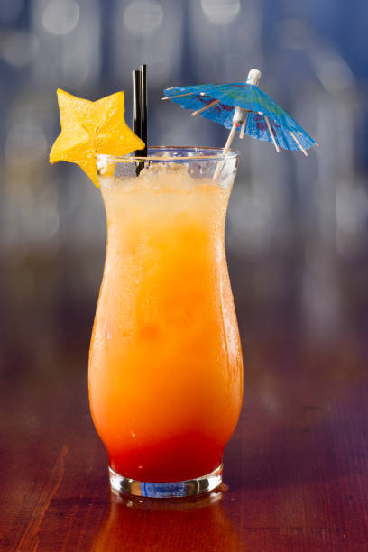 fruity cocktail fresh tropical juices mixed and served in a glass decorated with a carambola slice a parasol screwdriver drink stock pictures, royalty-free photos & images