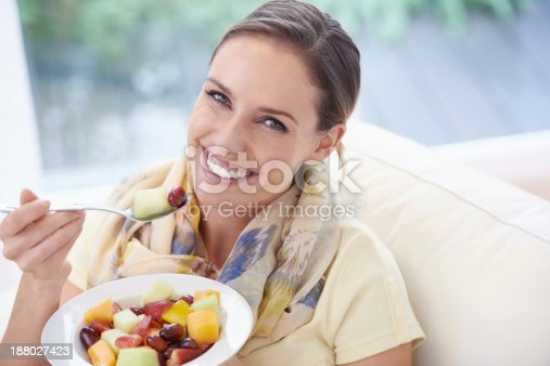 A young woman eating a fruit salad at home
