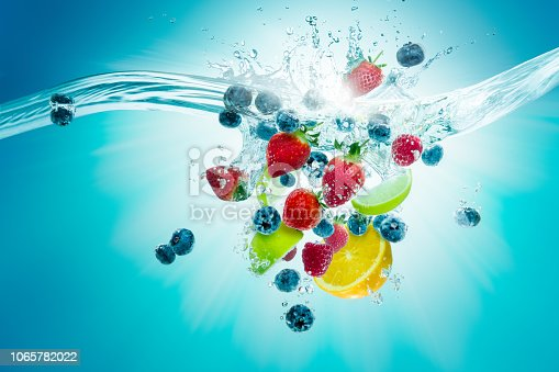A selection of fruit plunge into water creating a splash