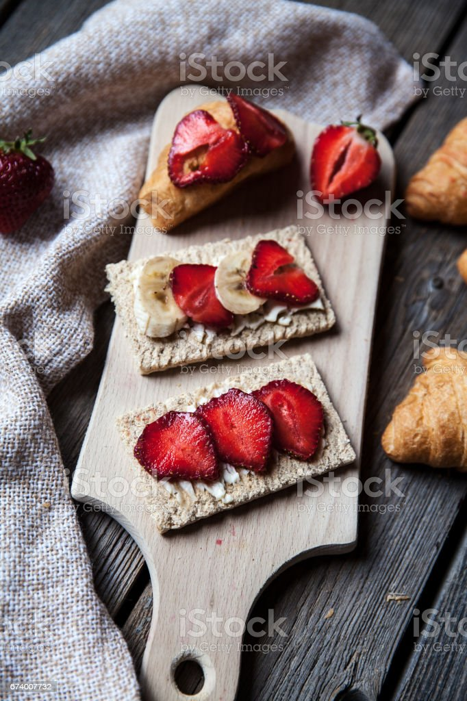 Fruity toast on wooden background. Strawberries royalty-free stock photo