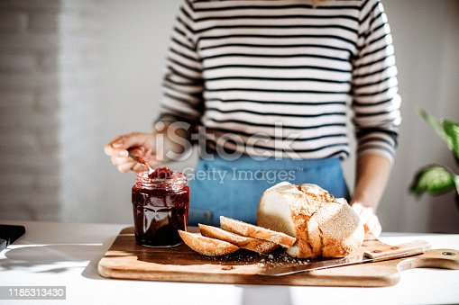 Close-up of unrecognizable woman making bread toast with jam