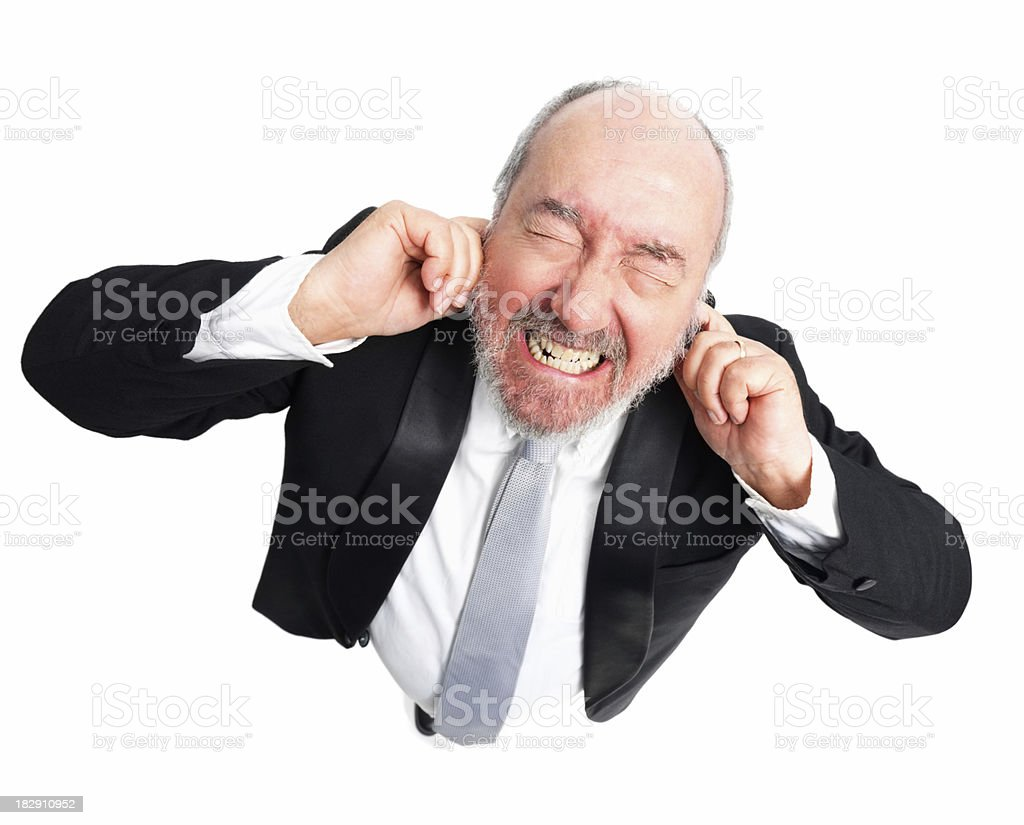 Frustated senior man with fingers in ears against white stock photo