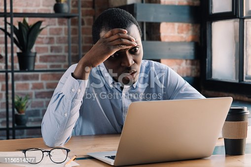 639105488 istock photo Frustrated african american business man sitting at his desk in modern loft office, holding hand on head, having problem with deadline 1156514377