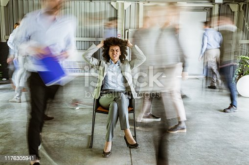 Angry black businesswoman pulling her hair while being surrounded by her colleagues who are walking in blurred motion.