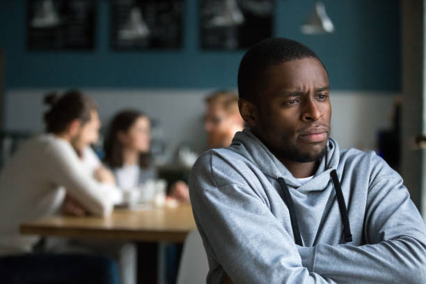 frustrated african man suffers from racial discrimination alone in cafe - disbarment stock pictures, royalty-free photos & images