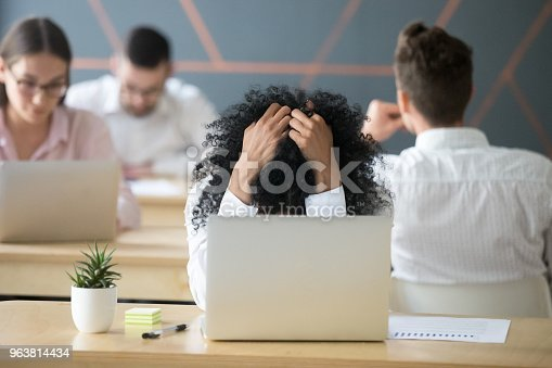 istock Frustrated african-american woman feeling despair in shared office with laptop 963814434